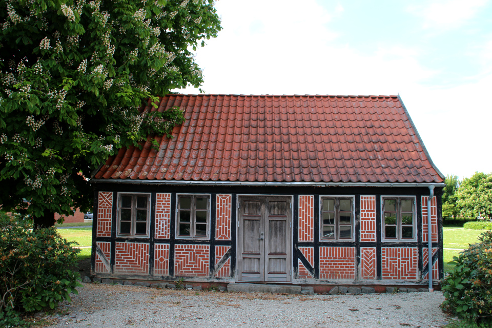 Цветущий конский каштан и фахверковый дом с фантазийными узорами из кирпичей