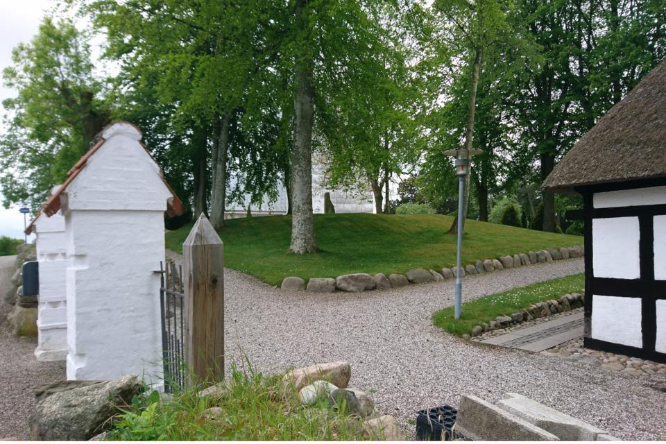 Курган с рунным камнем между церковью и домом приходского священника