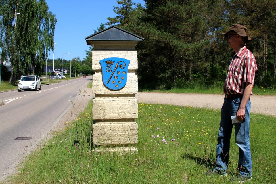 Герб города Гаммель Рю возле дороги, у въезда в город