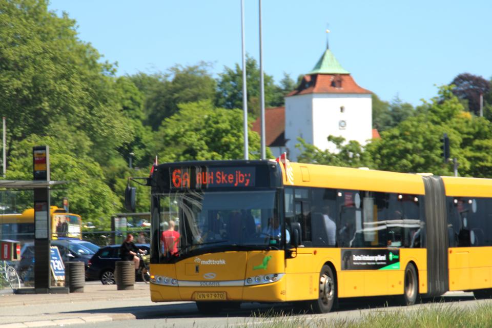 Городской автобус, украшенный флажками возле автобусной остановки