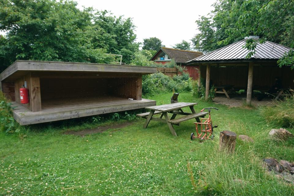 Домик-шелтер слева и крытый павильон со столами и скамейками слева
