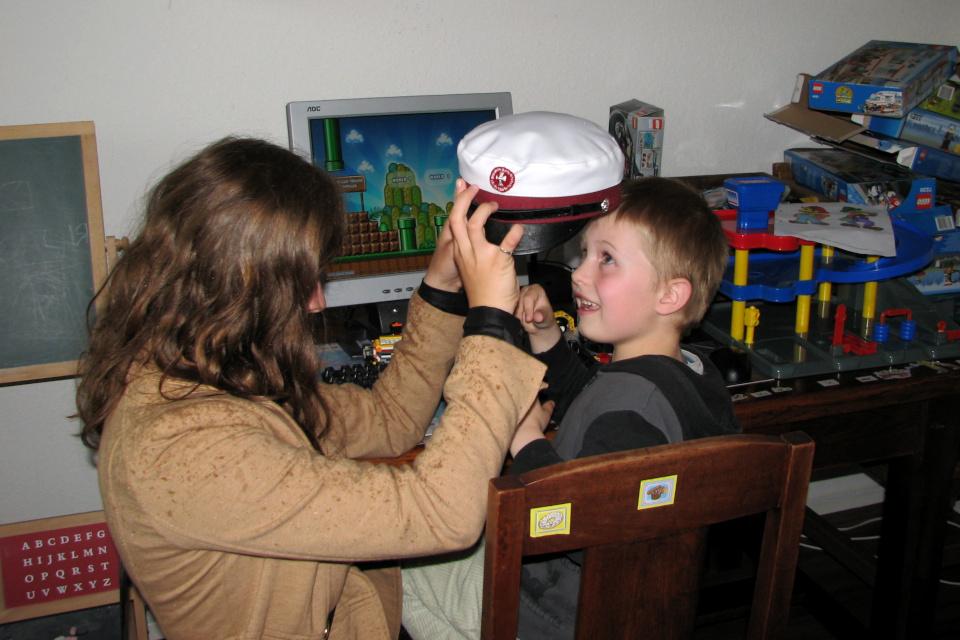 Моя дочка с гордостью показывает своему братику свою студенческую шапку