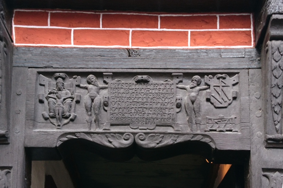 Украшение над входной дверью с символами святых и текстом на латинском языке