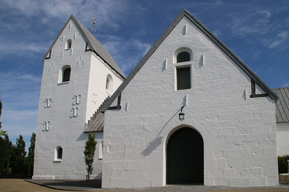 Северная сторона церкви с высокой башней и флюгером, построенной в 1753 году.