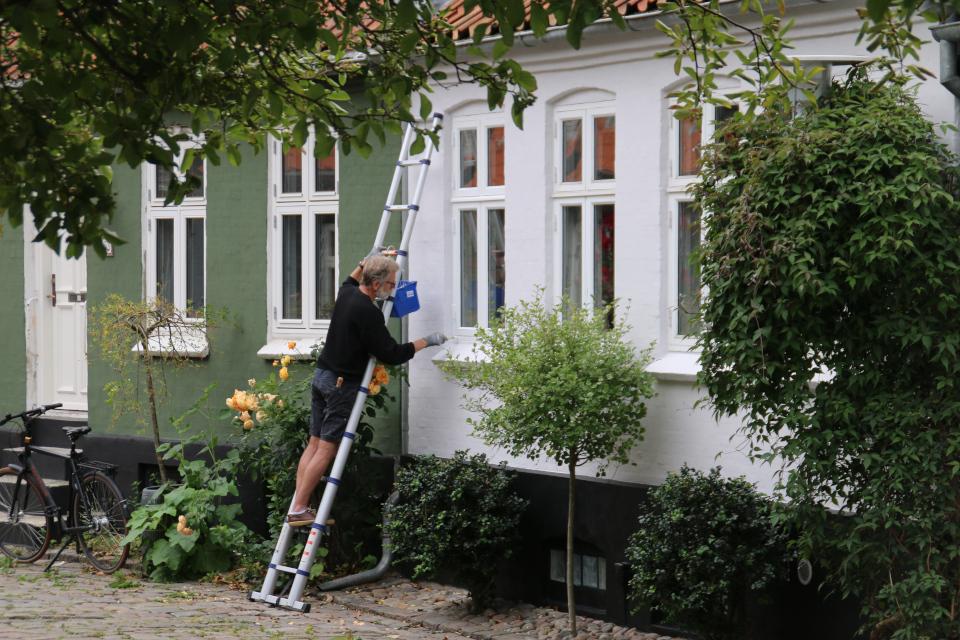 Хозяин дома окрашивает фасад своего жилища в белый цвет