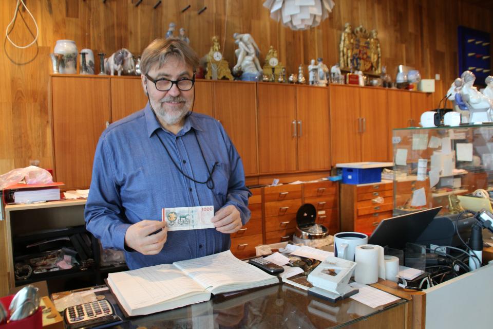 Продавец антикварного магазина с датской банкнотой 1000 крон