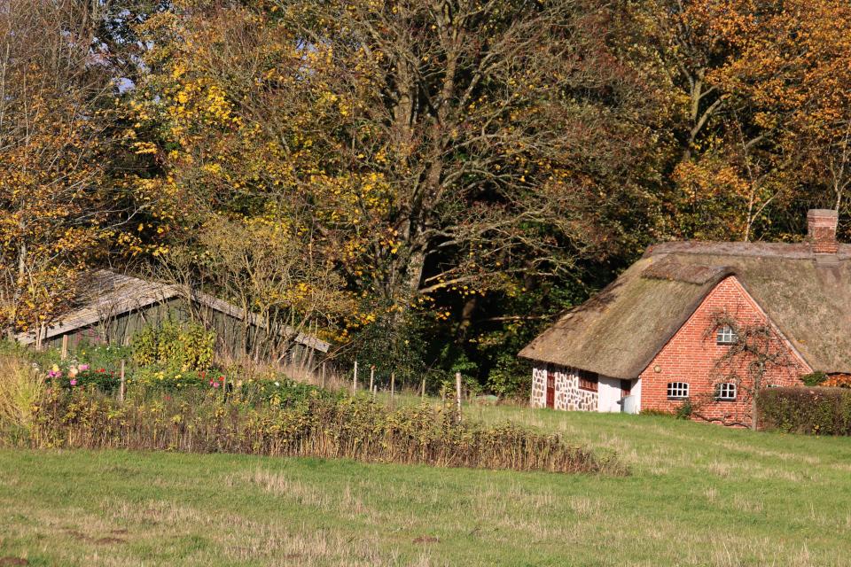 Каменный дом с соломенной крышей с пристройкой из кирпичей