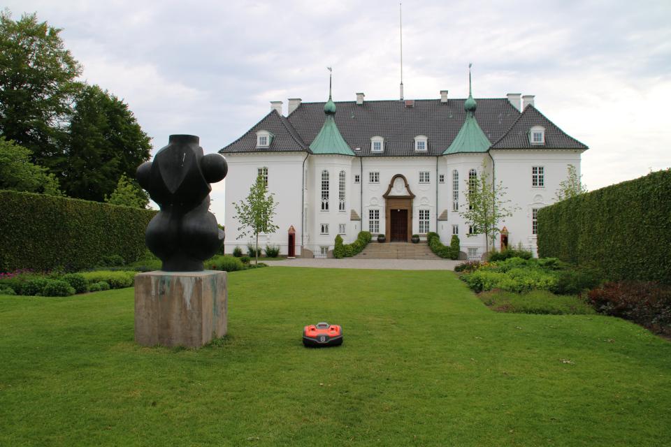 Газонокосилка-робот на газоне с клумбами и скульптурой принца Хенрика