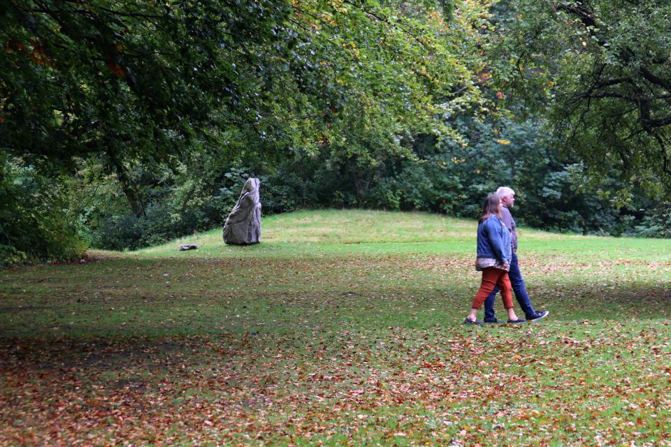 Каменная скульптура у подножья полуразрушенного кургана в парке Марселисборг