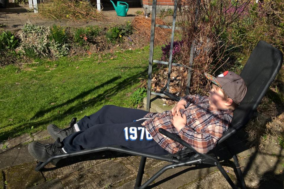 Мой сын отдыхает в саду, радуясь первым теплым весенним денькам