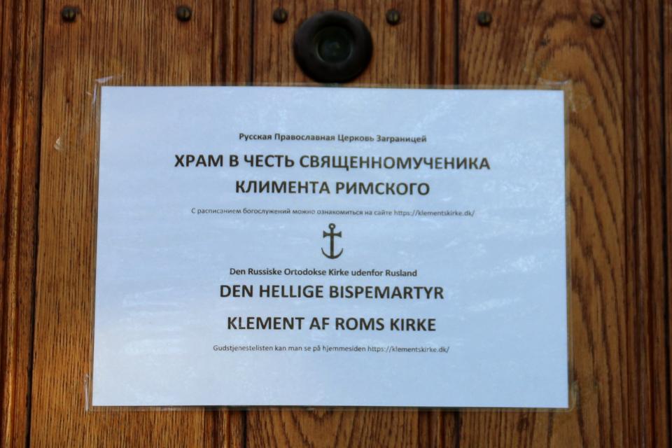 Информационная табличка на входной двери в Храм св. Климента Римского в Орхусе (Hl. Klement af Roms kirke i Aarhus) - бывший дом священника в Вибю. Фото 20 мая 2021, г. Вибю (Орхус), Дания