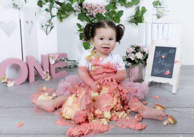 Cake Smash Den Bosch Meisje 1 jaar wat roze cupcake op eet Bij fotostudio Difa in Den Bosch