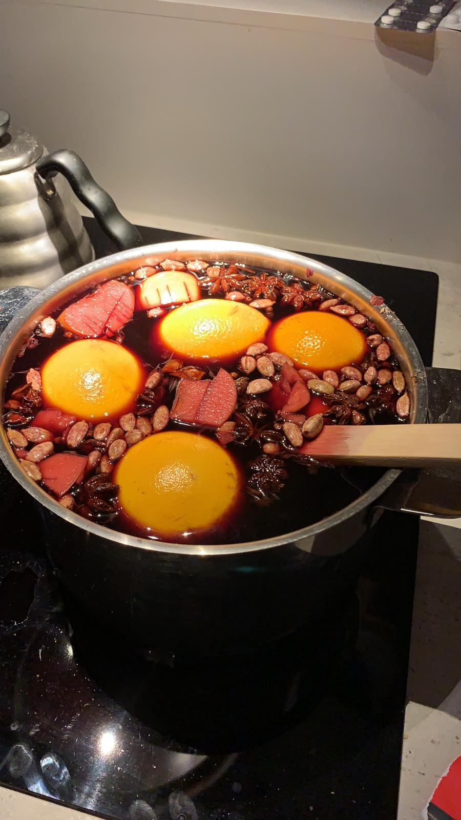 A big pot on a stove, filled with red wine with oranges and spices