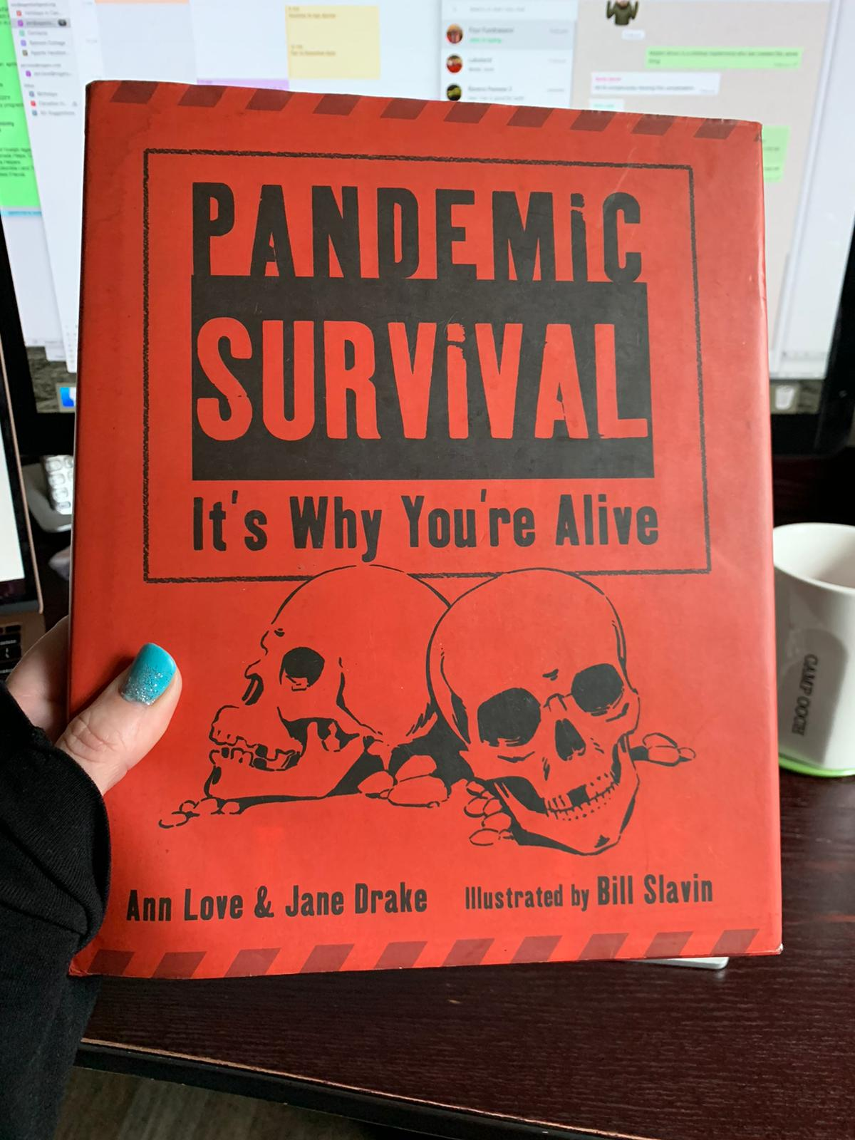 A hand with blue nail polish holding a book. The cover is an alarming shade of red, with two drawn skulls on it. The book title is Pandemic survival - it's why you are alive. Authors Ann Love and Jane Drake, Illustrated by Bill Slavin.