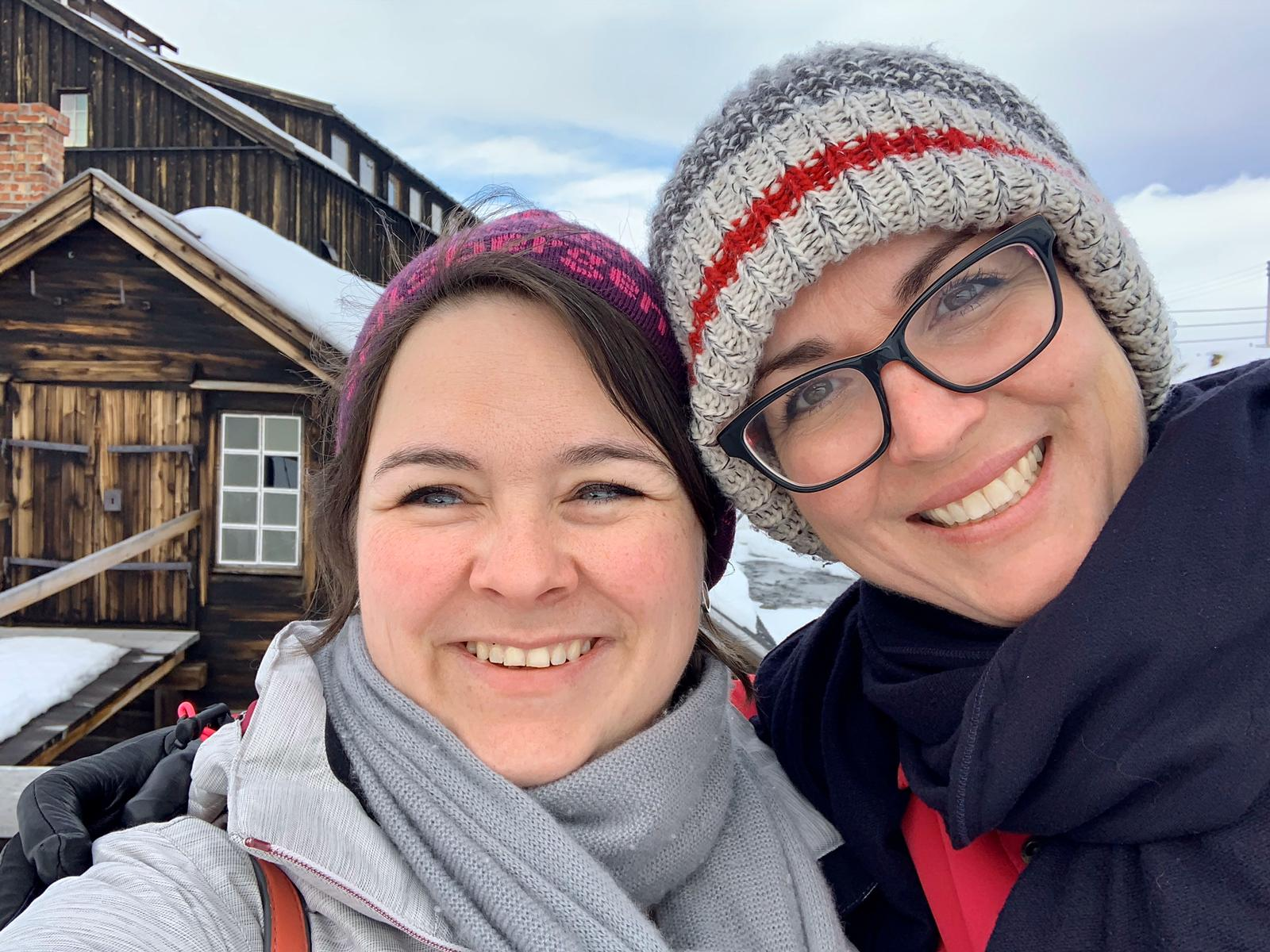 Beate and Jen in winter jackets and hats, in front of a very old wooden building covered in snow