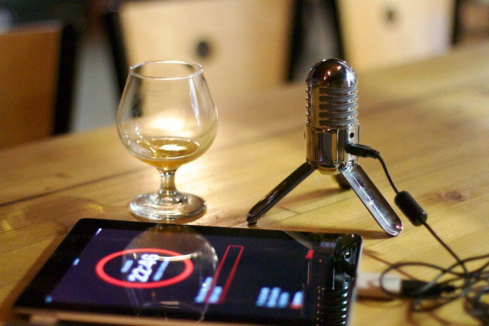 Podcast Equipment, Mikrofon, Tablet und ein Weinglas auf einem Tisch