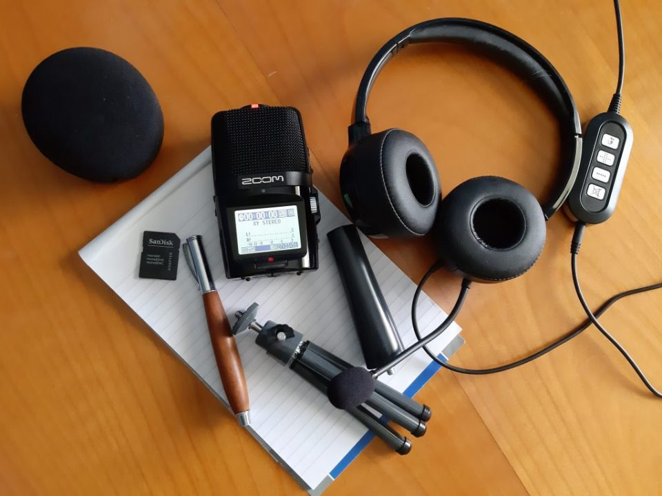 Podcast-Ausstattung, Headset, Zoom-Aufnahmegrät, Stativ, Speicherkarte, Stift und Schreibblock