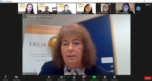 Redhaired woman on digital meeting, Freja poster in background.