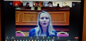 Blond woman in blue jacket, background one hall of EU in Brussels. In digital meeting.