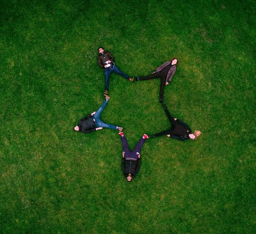 Five people laying on grass with their legs stretched out to form a five-sidestar.