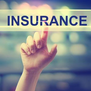 Insurance concept with hand pressing a button on blurred abstract background