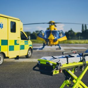Stretcher against ambulance car and helicopter of emergency medical service. Themes rescue, help and hope.