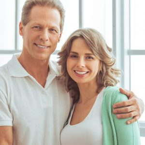 Portrait of happy beautiful couple in casual clothes cuddling, looking at camera and smiling