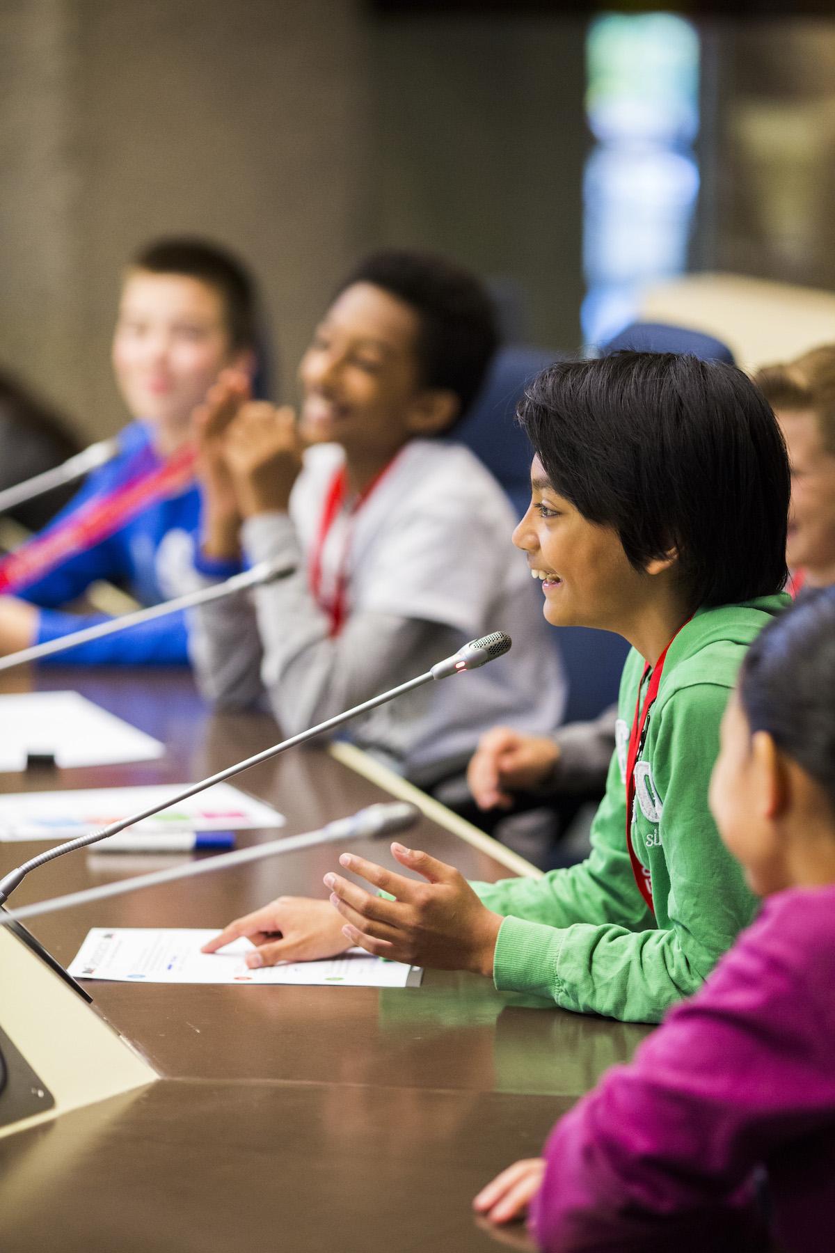 Groep kinderen in de raadzaal tijdens Schoolklassenbezoeken