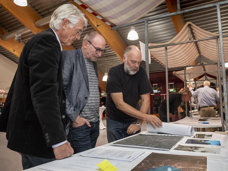 Drie mannen rond een marktkraam tijdens de ideeënmarkt