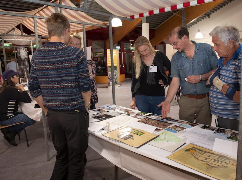 Vier mensen mensen rond een marktkraam tijdens de ideeënmarkt