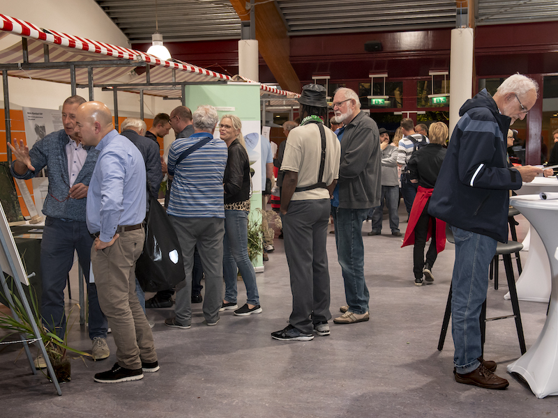Een groep mensen rond een marktkraam tijdens de ideeënmarkt