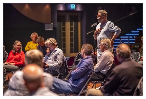 Man stelt vraag in microfoon tijdens raadconferentie kansongelijkheid