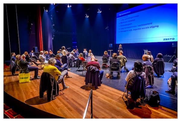 Podium met presentatiescherm tijdens raadconferentie kansongelijkheid