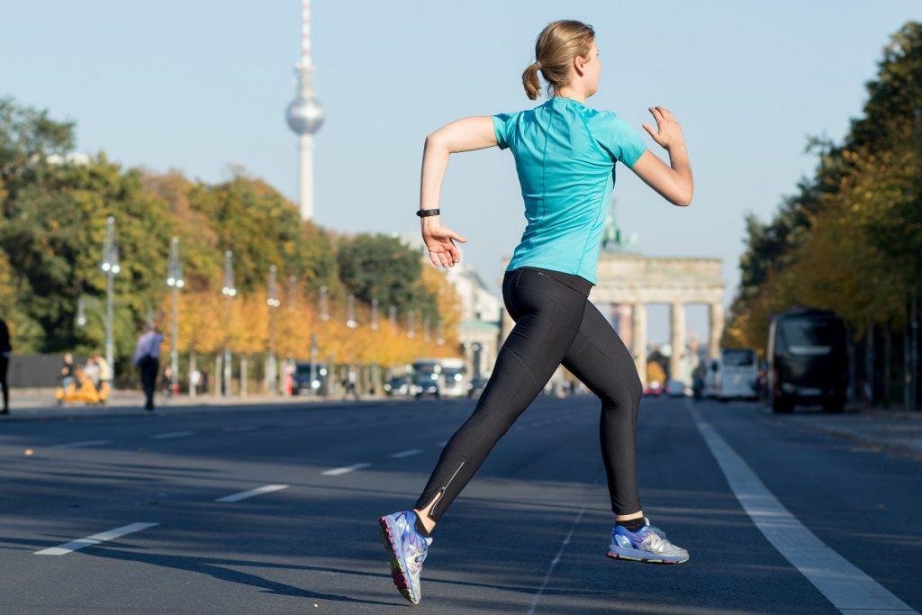 Frau läuft vor dem Brandenburger Tor.