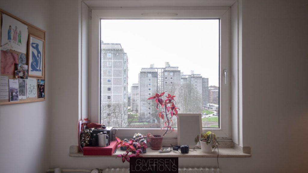 Kig gennem vindue i køkken til boligblok