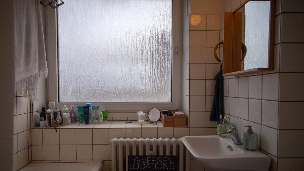 Lys gennem matteret rude i badeværels