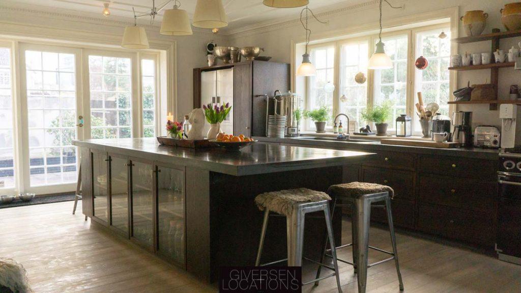 Lækkert lyst køkken på location med stolstole for enden af køkkenbord