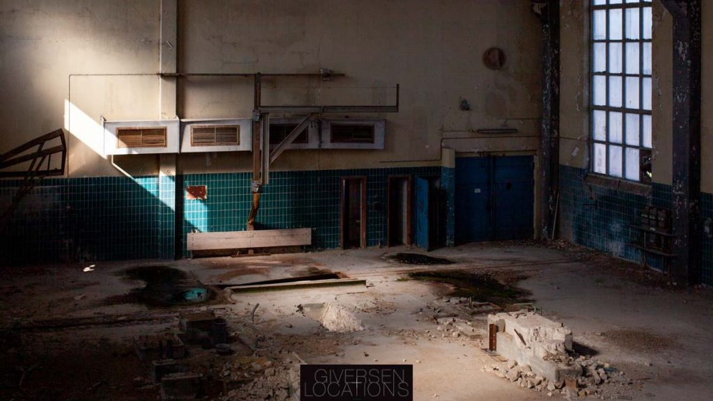 Lys falder ind gennem store vinduer i gammel fabrik