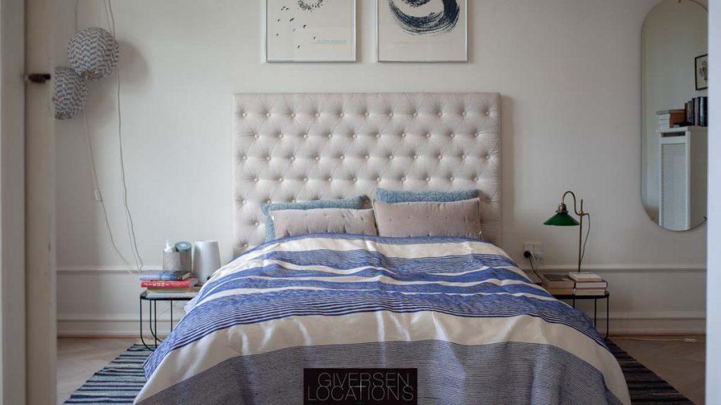 Flot soveværelse med store seng og stribet sengetæpep