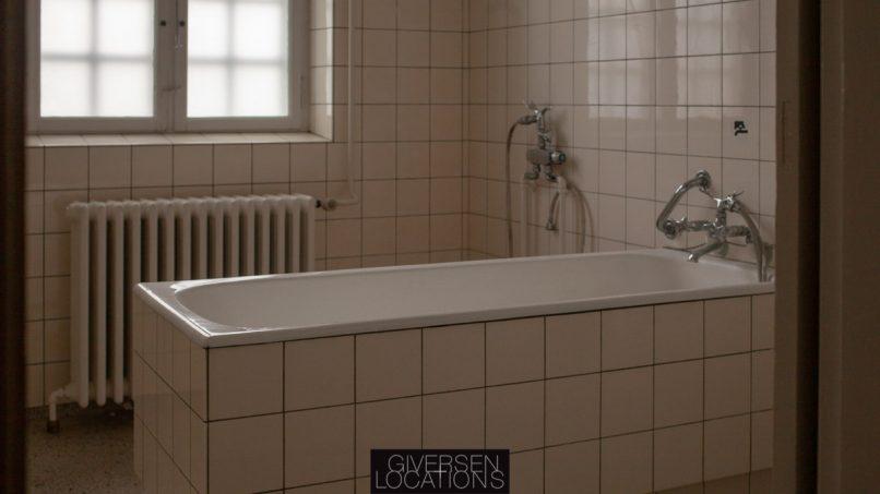 Lyset falder ind på badekar med gulnede fliser Separate baderum på et gammelt hospital