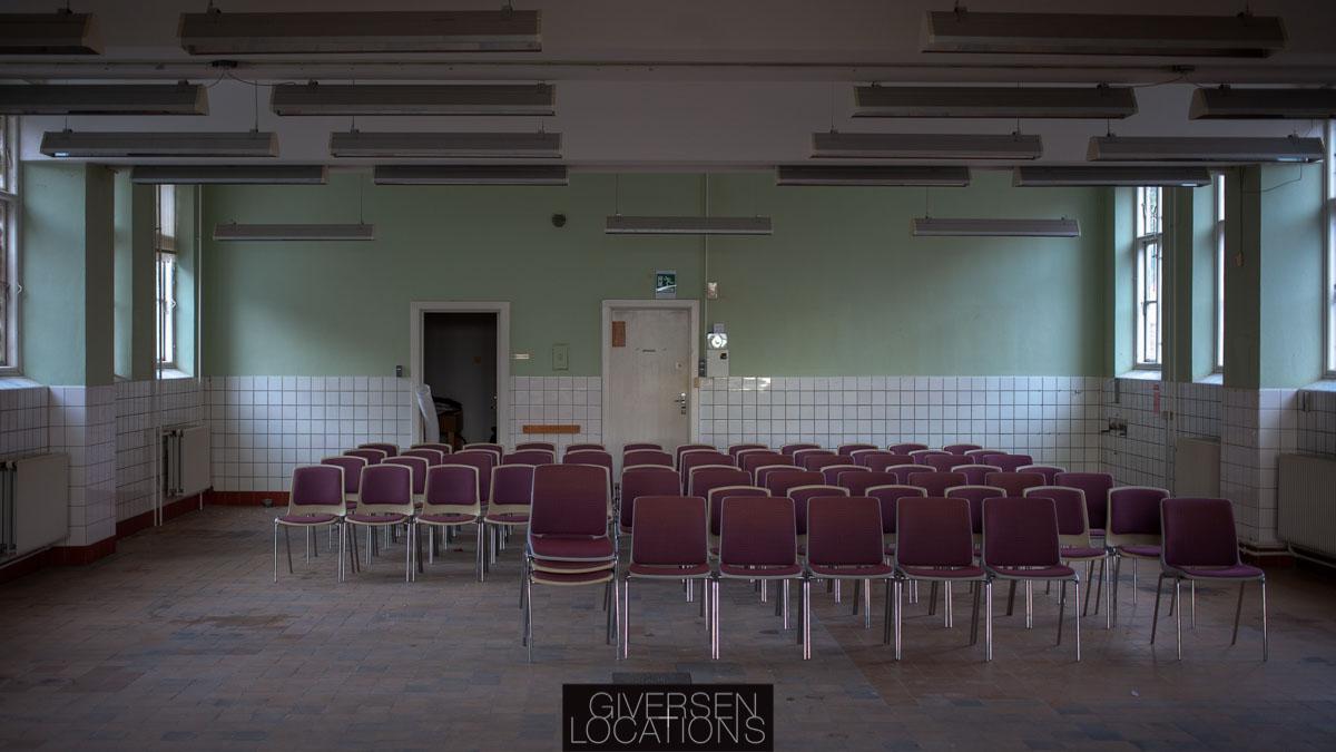 Stor sal med tomme stole på et gammelt hospital