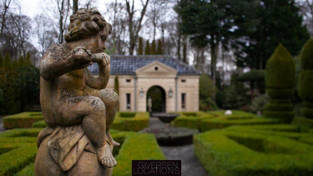 Smuk have med symmetrisk hække og, statuer og et havehus