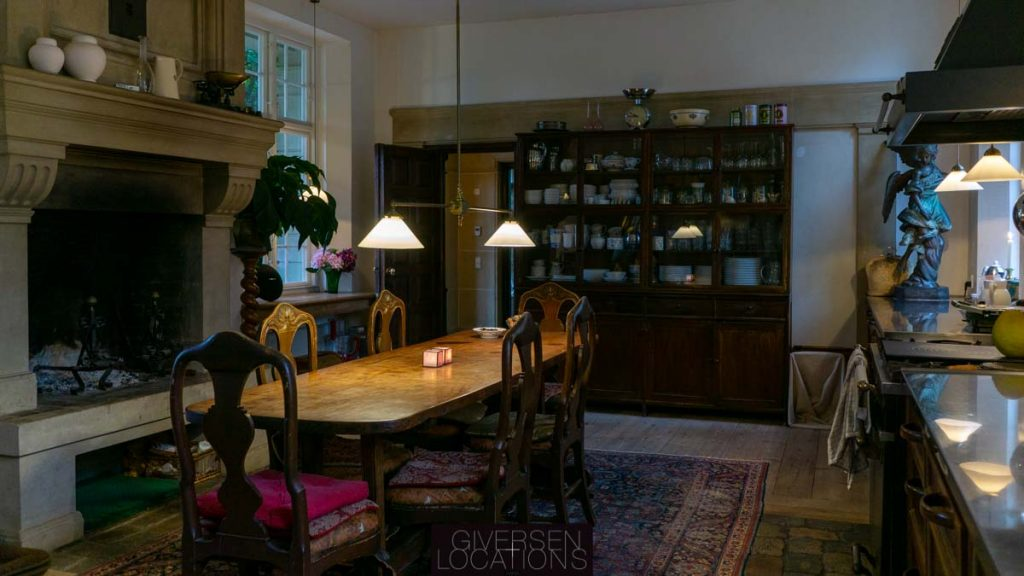 Smukt gammelt køkken med åben kamin og stort træbord