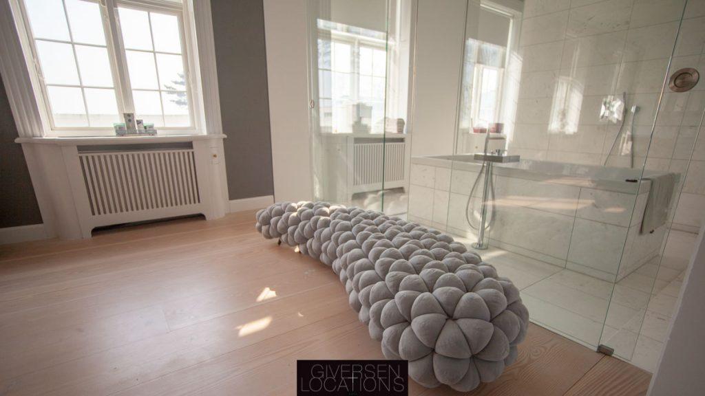 Siddeplads i luksuriøst soveværelse med kig til luksubadeværelse