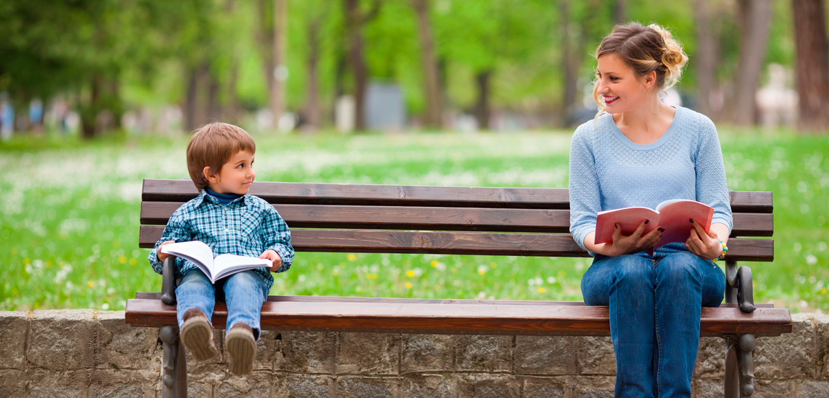 Woman and child on a bench with books