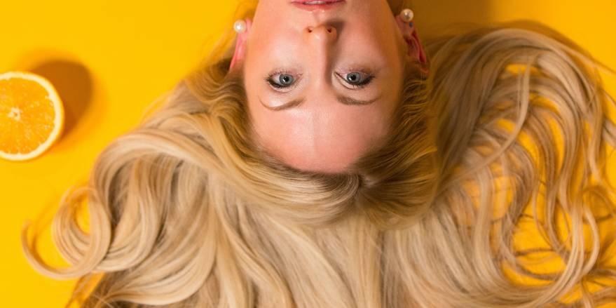 Kvinde på gul baggrund flot hår og appelsin
