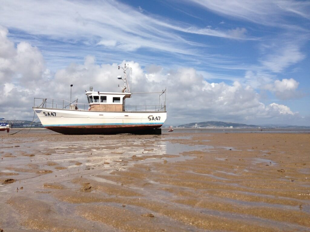Boat on the shore at Mumbles - low tide.