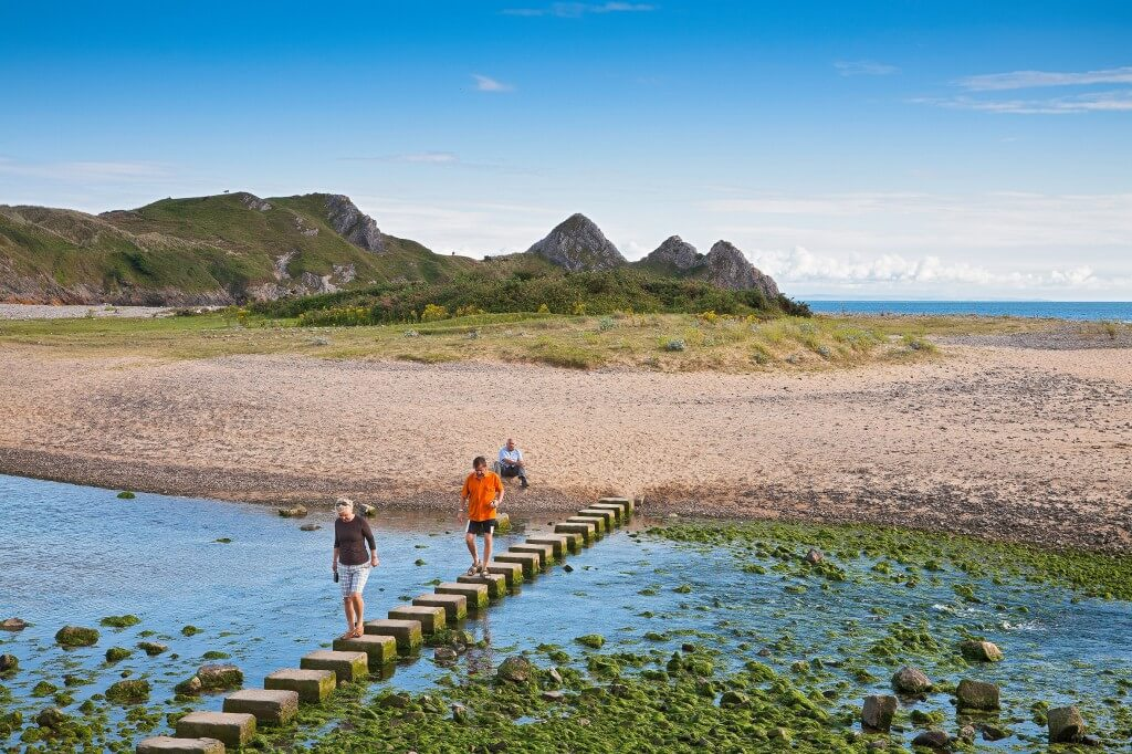 People walking across the stepping stones at Three Cliffs Bay