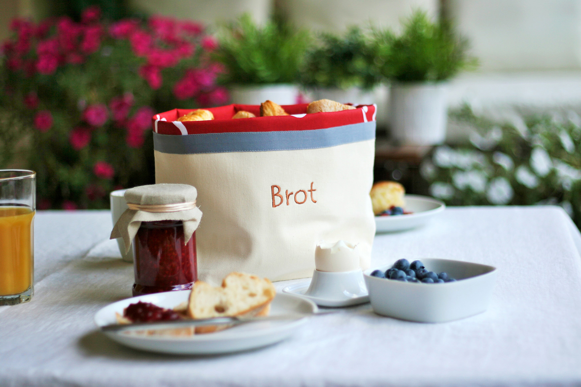 Offener Brotbeutel auf gedecktem Frühstückstisch