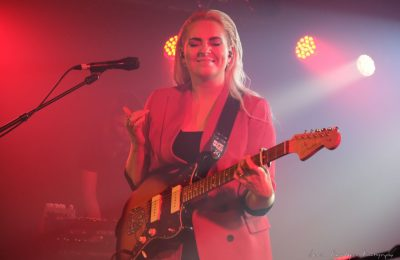 Eivor facing the camera with her eyes closed while holding a guitar.